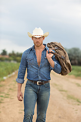 rugged cowboy walking on a dirt road in rural American with a saddle over his shoulder