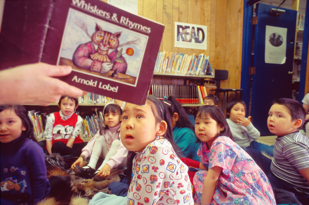 Alaska . Barrow . Elementary schoolchildren have a book read to them at the local library .