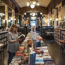 A woman leafs through a book at the newly refurbished section of Caffe San Marco in Trieste, Italy.