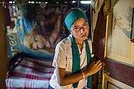 Kenia, 14, stands at the doorway of her bedroom in Leaper Lempira, outside of Santa Rosa de Copan, Honduras, March 10, 2014. Kenia has gone through several several plastic surgeries to repair the ear that was almost nonexistent sense she was born.