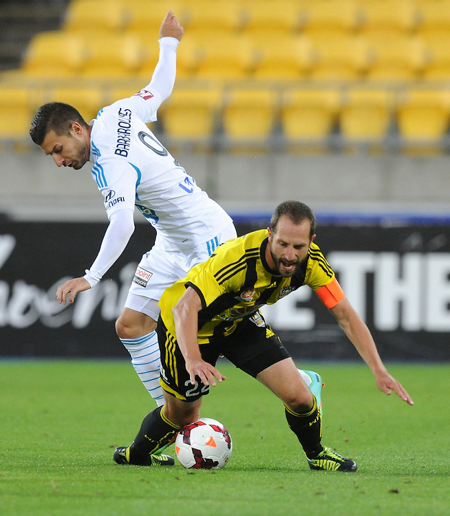 Melbourne Victory's Kosta Barbarouses, left, tackles Phoenix's Andrew Durante in the A-League football match at Westpac Stadium, Wellington, New Zealand, Saturday, Januray 18, 2014. Credit:SNPA / Ross Setford
