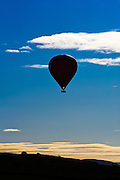 A hot air balloon, floating over the Eden Valley, Cumbria, with flame showing, evening sky.
