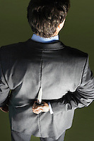 Mid-adult businessman standing holding knife behind back back view