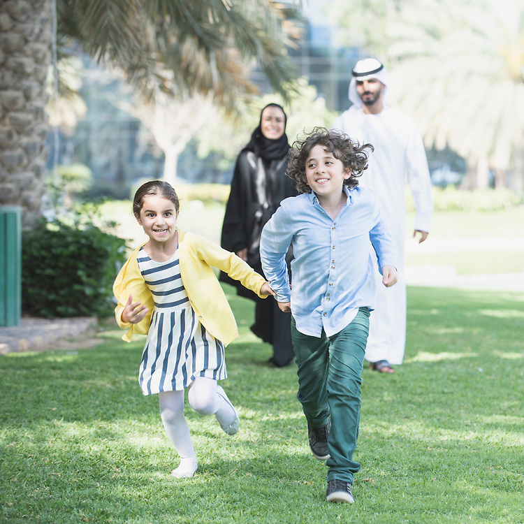 Happy smiling children from traditional Arab Emirati family race eachother through a park as mother and father look on