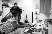 A neighborhood teen hugs Shameka while she cleans a pair of sneakers. Sept. 2012