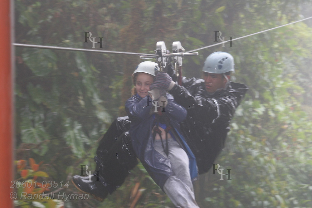 Ecoteach kid Soley Hyman (age 9) rides tandem with guide on zipline through the Monteverde cloud forest on Sky Trek cable; Monteverde, Costa Rica.