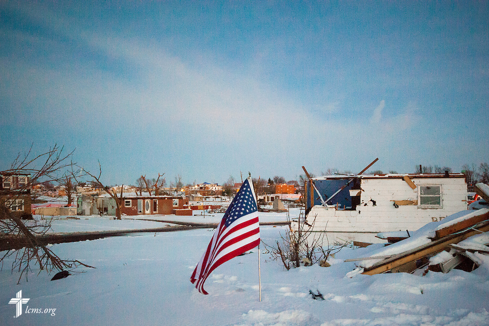 A flag is perched next to a damaged home on Wednesday, Dec. 18, 2013, in Washington, Ill. Nearly two dozen tornadoes plowed through Illinois in November, killing a total of seven. LCMS Communications/Erik M. Lunsford