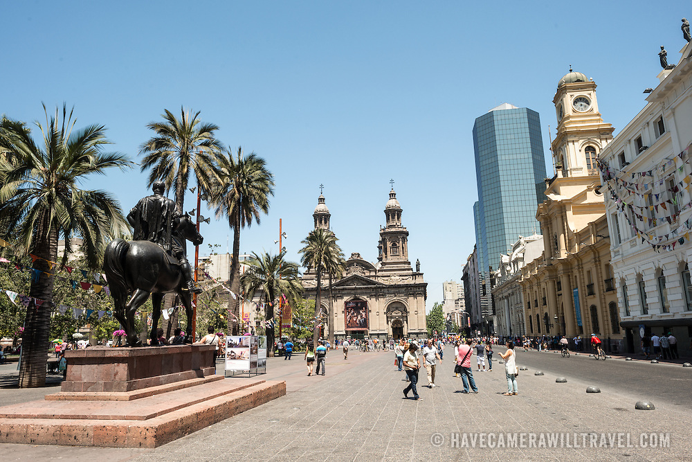 Plaza de Armas in the center of Santiago de Chile, with a statue of Don Pedro de Valdivia at left and the Metropolitan Cathedral of Santiago in the center of frame.