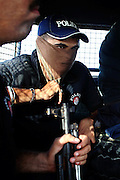 An armed member of the AVCC, (Anti-Violence Crime Cell) a special police unit mostly involved in anti-terrorism operations and kidnap cases in the city of Karachi, is preparing to raid a cluster of houses on the outskirts of the city on their search for a kidnap suspect during a fake ransom meet up with the criminals.