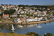Salcombe town and estuary from Portlemouth Down. A sailboat makes its way to the sea in the early morning.