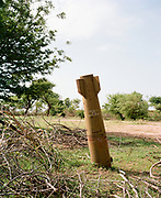 "NUBA MOUNTAINS, SUDAN – JUNE 9, 2018: An unexploded bomb can be seen on the property of the former State Hospital in Kouda, where four parachute bombs were dropped in 2014. Miraculously, none of the ordinances exploded, and can still be seen protruding from the ground surrounding the hospital compound.<br /> <br /> In 2011, the government of Sudan expelled all humanitarian groups from the country's Nuba Mountains. Since then, the Antonov aircraft has terrorized the Nuba people, dropping more than 4,080 bombs on hospitals, schools, marketplaces and churches. Today, vestiges of the Antonov riddle the landscapes of daily life, where more than 1 million Nuba live in famine conditions – quietly enduring the humanitarian blockade intended to drive them out of the region. The skies are mostly clear. Yet the collective memory of the bombings remains an open wound, and the Antonov itself a persistent threat. So frequent were the attacks that the Nuba nicknamed the high flying aircraft and its dismal hum: ""Gafal-nia ja,"" they would declare, running to the hillsides. ""The loss of appetite has come."""