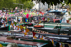 Little Venice, London, April 30th 2017. Narrowboaters from all over the uK gather for the annual Canalway Cavalcade, held on the May Day Bank holiday weekend, organised by the Inland Waterways Association, where boaters get the chance to display their immaculately prepared and brightly painted craft as well as compete in various manoeuvring tests. PICTURED: Narrowboats are moored side by side in Paddington basin where the Regents Canal ends and the Grand Union Canal begins.<br /> Credit: ©Paul Davey<br /> To licence contact: <br /> Mobile: +44 (0) 7966 016 296<br /> Email: paul@pauldaveycreative.co.uk<br /> Twitter: @pauldaveycreate