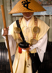 Buddhist monk collecting alms on street in Kyoto Japan