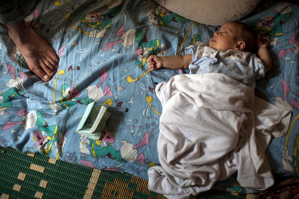 27/06/2013 Shatila refugee camp, Beirut: A newborn Syrian refugee boy sleeps next to the birth papers his family received from the hospital in Beirut where he was delivered. Since 2011, housing costs have quadrupled for people fleeing the conflict in Syria, and work is scarce or extremely low-paying. Estimates have placed the number of Syrian refugees in Lebanon at well over 500,000 people.