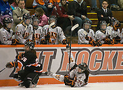 2012/01/20 - Bufalo State Christina Zandri and RIT's Kourtney Kunichika fall in front of the RIT bench during a 5-2 RIT victory in Rochester, N.Y. on January 20th. RIT wore special camouflage jerseys in support of the Wounded Warriors program.