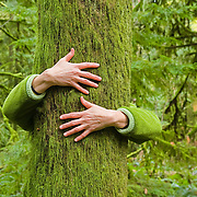 A photo of a woman hugging a tree in a rainforest on Vancouver Island in British Columbia in Canada