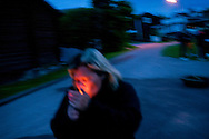 A woman lighting a cigarette at the village party in V&auml;stanvik, Sweden<br /> <br /> Midsummer  is one of the most important holidays of the year in Sweden, and probably the most uniquely Swedish in the way it is celebrated. The celebrations in the villages around the city Leksand go on for numerous days, with village parties, dancing and the raising of maypoles.