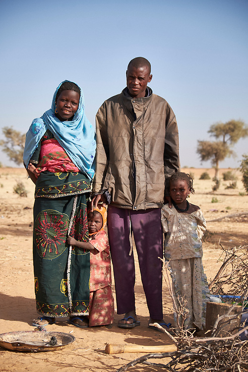 Mahamadou Kiari with wife Adama and children in a camp of internally displaced people by the side of the road on the highway outside of Diffa, Niger on February 14, 2016. Caritas undertook a distribution of two blankets per family in January, 2016. Most of the displaced people are from the town of Chilori, Niger on the border with Nigeria and fled when the village was attacked by Boko Haram. <br /> <br /> Mahamadou - 'Boko Haram stole all my crops for the season after we fled the village. We have been here for about 3 months now and came from a village in Niger at the border.'
