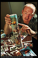 Story:  Custom made candle made to memorialize the trio of terrorist attacks of September 11, 2001, on the first anniversary of the tragedy.<br /> Date: Friday September 6, 2002<br /> Caption:  Detroit Free Press chief photographer J. Kyle Keener works in the studio gluing miniature photo prints of news photographs from  the September 11, 2002, trio of terrorist attacks in New York City, Washington D.C. and Shanksville, PA, for a custom candle memorial photo illustration in preparation for the one year anniversary of the tragic events.  Keener used the self-timer on his camera to shoot the prop building process that he often documents for later use in lectures to photographic groups across the country.