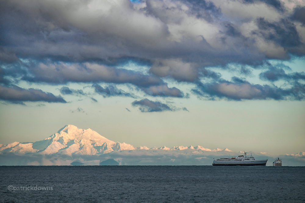 "Mt. Baker, covered in 188"" of snow this season, glows in the sun as seen from Port Angeles, about 60 miles away to the west. The clouds in between over the Strait of Juan de Fuca look ominous. The ship is the MV Coho, a ferry that runs between Port Angeles, WA and Victoria BC."