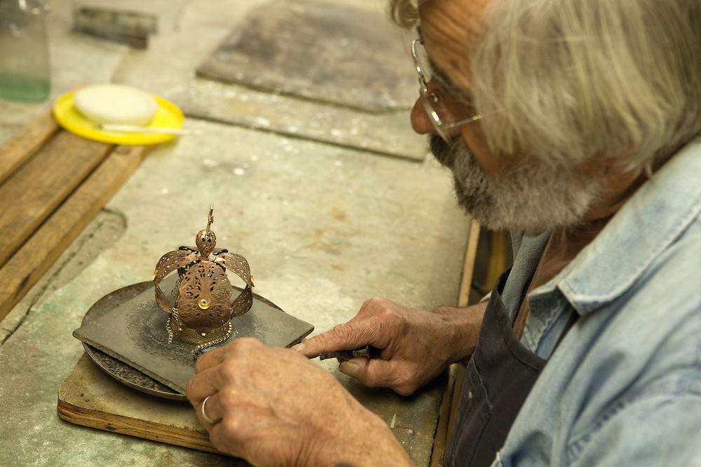 Martin places a band wih mounted crystals around the circlet of a crown before soldering it on.