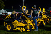 WASHINGTON, USA - September 15: A family takes a break on a display of large mowers at the Great Frederick Fair in Frederick, Md., USA on September 15, 2017. The fairs often also have an agricultural focus showcasing local farms, animals, and farming equipment.