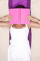 Woman covering face with book while lying on picnic blanket
