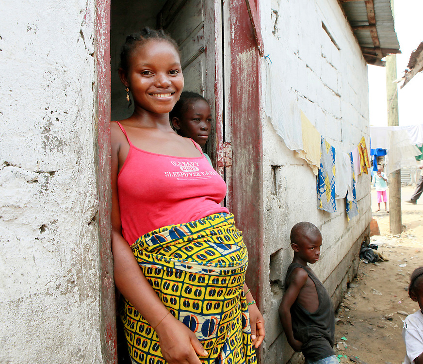 Kumba, a young pregnant mother, stands in the doorway of her home in the West Point area of Monrovia, Liberia, Sunday, March 6, 2011.  Access to health care and information about wellness during pregnancy is a key challenge for millions of women around the world.  Kumba is one of thousands of women who are part of a global conversation about International Women's Day 2011. (Stuart Ramson for United Nations Foundation)