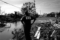 A New Orleans Emergency Medical Services worker looks over the flooded and destroyed landscape of the once lively streets of the lower ninth ward over one month after hurricane katrina made lanfall 8 October 2005 New Orleans Louisiana.  (photo by Darren Hauck)
