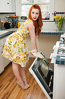 Full length portrait of a young woman standing by an open oven