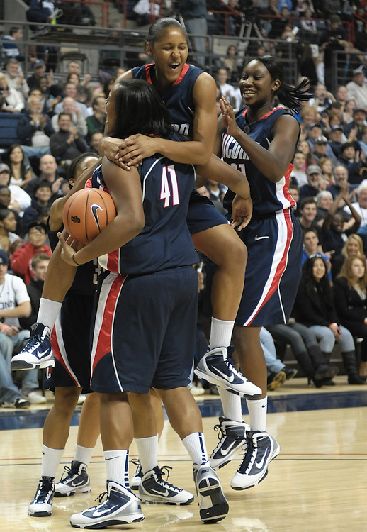 Connecticut's Maya Moore jumps up on Kaili McLaren (41) as teammate Tina Charles, right, congratulates Moore after winning the slam dunk competition team event with Stanley Robinson at the First Night NCAA basketball exhibition, in Storrs, Conn., Friday, Oct. 16, 2009. (AP Photo/Jessica Hill)
