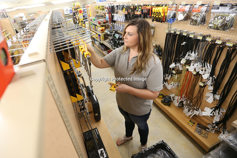 Jill Timmons, stocks the shelves with wrenches at the family's new hardware store, Westside Hardware, located on Cliff Gookin Boulevard.
