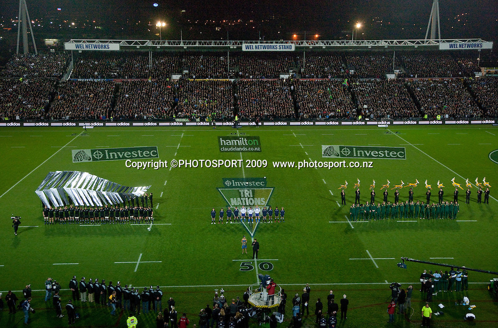 A general view of the teams lined up for the national anthems with a large silver fern design behind the All Blacks before the Tri Nations Rugby - All Blacks v South Africa, won 32-29 by the Springboks at Waikato Stadium, Hamilton, New Zealand, Saturday 12 September 2009. Photo: Stephen Barker/PHOTOSPORT