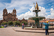 Visitors taking photo at fountain in Plaza de Armas with La Compañia church in background; Cusco. Peru.