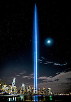 World Trade Center Memorial lights from Jersey City with mooon, Freedom Tower, on the Hudson River.