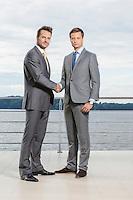 Full length portrait of businessmen shaking hands on terrace
