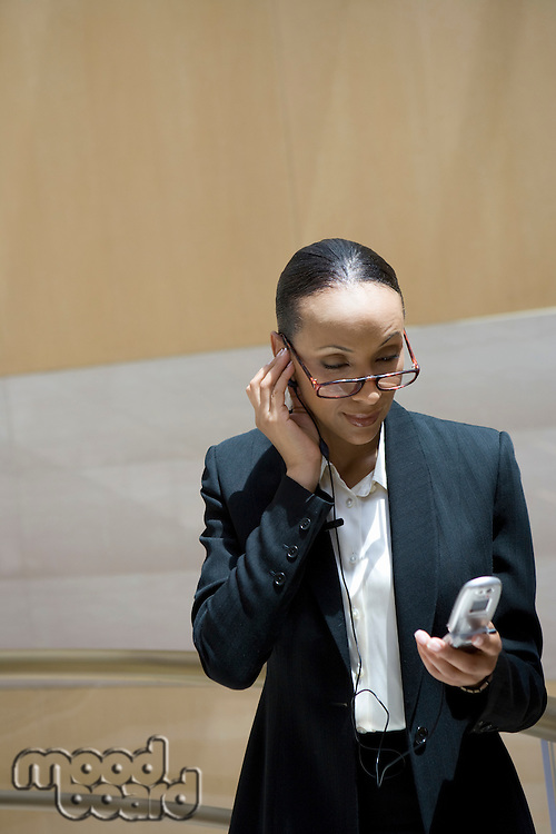 Business woman using mobile phone, indoors