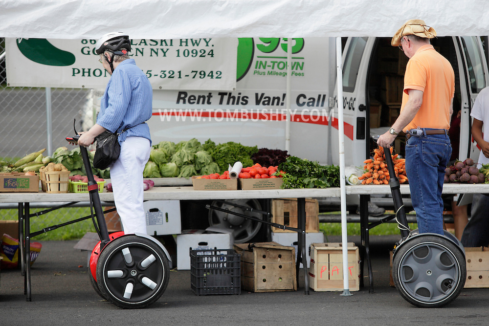 Wurtsboro, NY - An elderly couple riding on Segway Personal Transporters look vegetables for sale at a farmers market show at Wurtsboro Airport on Aug. 30, 2009.