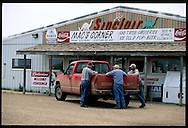 Three locals chat over pickup truck outside grocery store; Stephan, South Dakota