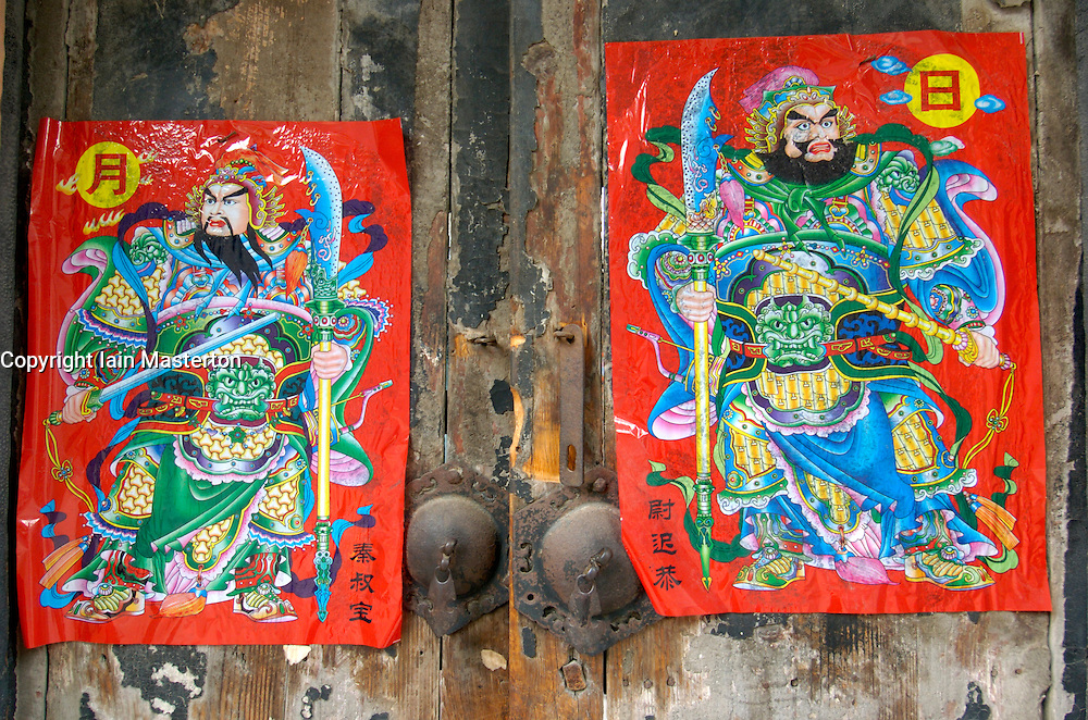 Detail of traditional pictures to attract good fortune hung on old wooden doors to a house in Beijing