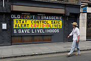 During the UK's Coronavirus pandemic lockdown and on the day when a further 255 deaths occurred, bringing the official covid deaths to 37,048, <br /> a man walks past a stencilled message outside the Old Compton Street Brasserie which carries the government's message about 'Stay Alert, Control Covid-19, Save Lives' plus a message from retail business owners and workers, to Save Livelihoods, on 26th May 2020, in London, England.