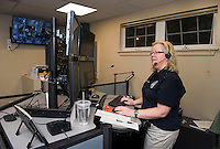 Dispatcher Karen Craver working at the new Dispatch Center in the Gilford Police Dept during the Open House tour on Thursday evening.  (Karen Bobotas/for the Laconia Daily Sun)