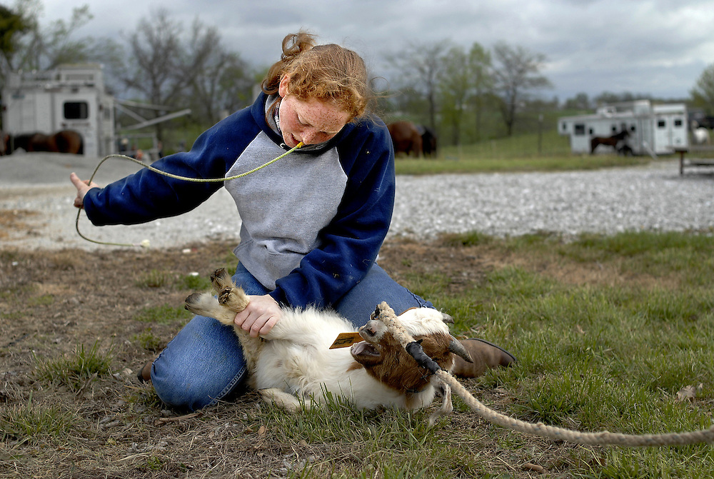 """Casey Chasteen, 18, is a two-time Missouri state champion in goat tying. Fluid with her tying technique, Casey practices the motions until they are flawless.  Standing apart from other teenagers during warm-ups for competition Casey explains, """"Sometimes I get to where I just have to think it all through. I do my own thing."""""""