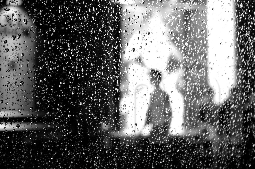 Silhouette of a man walking in the street on a rainy night in Ho Chi Minh city, Vietnam, Asia