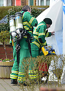 © Licensed to London News Pictures. 13/04/2013. Ruislip, UK Ambulance staff with breathing apparatus and medical equipment enter.. Police and ambulance crews at the scene where a woman and two children have been found dead at a house in Ruislip, West London. Police were called by London Ambulance Service at approx 1840 hrs on Friday 12 April to reports of a woman and two children found deceased at an address in Midcroft Road. Photo credit : Stephen Simpson/LNP