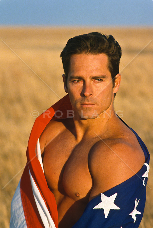 Shirtless man wrapped in an American flag