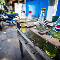 Jan 3, 2013 - Fuel is often sold by the litre in used soda drink bottles in road side stands, convient for passing bikes in the Cambodian capital city of Phnom Penh. <br /> <br /> Story Summary: Amidst the feverish pace of Phnom Penh&rsquo; city streets, a workhorse of transportation for people and goods emerges: Bicycles, motorcycles, scooters, Mopeds, motodups and Tuk Tuks roam in place of cars and trucks. Almost 90 percent of the vehicles roaming the Cambodian capital of almost 2.3 million people choose these for getting about. Congestion and environment both benefit from the small size and small engines. Business is booming in the movement of goods and and another one million annual tourists in Cambodia&rsquo;s moto culture.