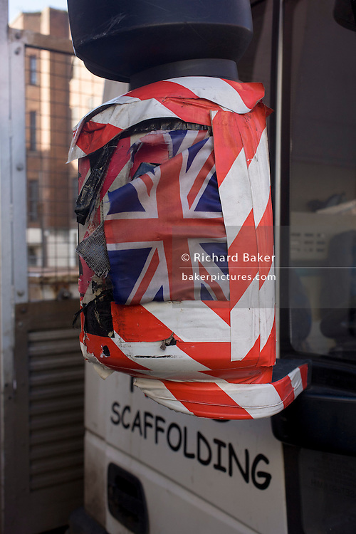 A Union Jack taped with stripy tape, on the wing mirror of a scaffolding van, in Mayfair, London.