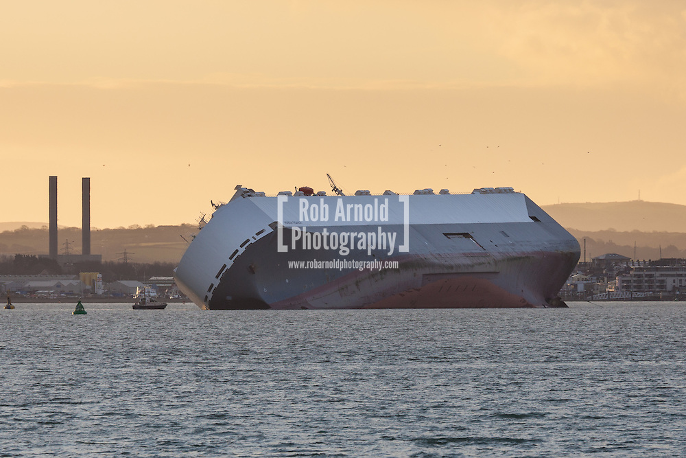The Singapore registered cargo ship, Hoegh Osaka, lying on Bramble Bank in the Solent, between Hampshire and the Isle of Wight today, 7th January 2015. The car carrier was deliberately run aground on 3rd January 2015 following the ship developing a list. The ship is now listing at a 52-degree angle. A salvage operation by salvage company, Svitzer, was due to take place today, but is believed to have been postponed due to the ship taking on more water than was previously thought.
