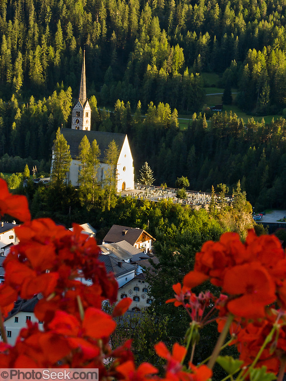 "Red geraniums frame the main church and cemetery in the town of Scuol, Switzerland, Europe. Published in Ryder-Walker Alpine Adventures ""Inn to Inn Alpine Hiking Adventures"" Catalog 2007."